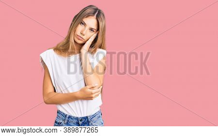 Beautiful caucasian woman with blonde hair wearing casual white tshirt thinking looking tired and bored with depression problems with crossed arms.