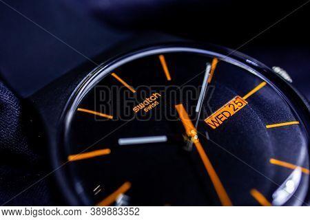 Rome, Italy 07.10.2020 - Swatch Logo On Black Wristwatch Dial Swiss Made Quartz Watch Orange Arrows