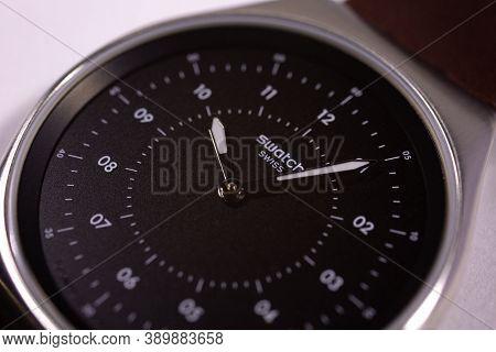London, Gb 07.10.2020 - Swatch Logo On Black Wristwatch Dial Of Swiss Made Quartz Watch. Metal Case,