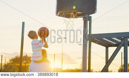 Father and son playing basketball on the court at sunset