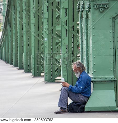 Budapest, Hungary - July 21, 2015: Man Resting At The Liberty Bridge In Budapest Hungary Reading A B