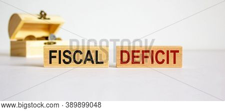 Concept Words Fiscal Deficit On Blocks On A Beautiful White Background, Small Chest With Coins. Busi