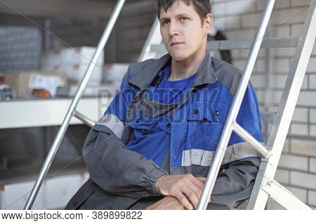 Young Man Sad In Thought At The Workplace. Concept Of Downsizing And Job Loss