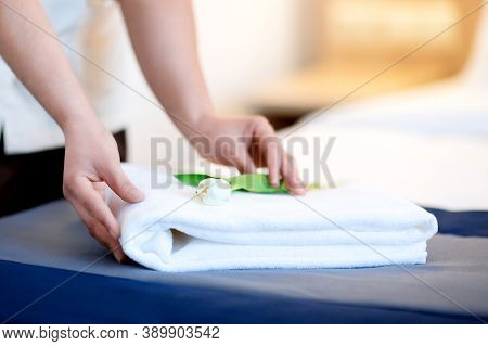 The Maid Folds A Fresh White Towel In The Hotel Room. Hands Close-up. Decorates With A White Tulip