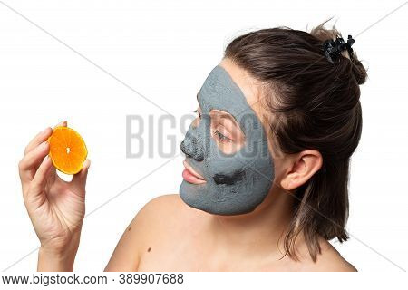 Cheerful Caucasian Woman With A Clay Or A Mud Mask On Her Face Holding Orange Or Tangerine Over Whit