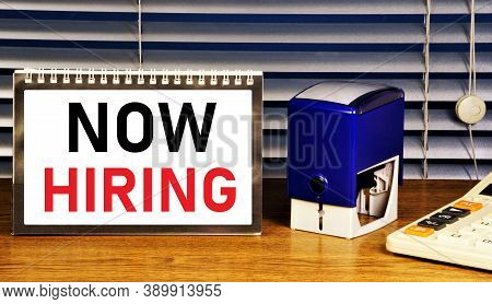 Now Hiring. Text Label In The Planning Table. Employment According To The Rules Of The Agreement Of