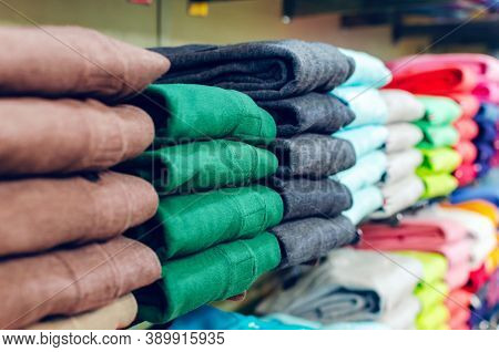 Multicolored Clothes Stacked In Piles On A Rack In A Clothing Store.