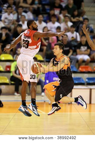 KUALA LUMPUR - OCTOBER 28: Firehorse's Lau Bik Ing (black) sails past Dragon's Moala Tautaa #33 to score in a Malaysia National Basketball League match on October 28, 2012 in Kuala Lumpur, Malaysia.