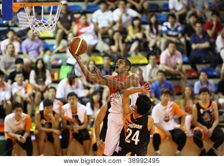 KUALA LUMPUR - OCTOBER 28: Dragons' Satyaseelan (white) rolls in the ball to score against Firehorse team in a Malaysia National Basketball League match on October 28, 2012 in Kuala Lumpur, Malaysia.