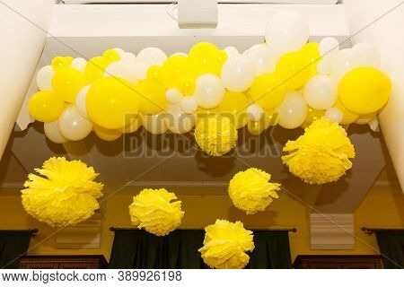 Decorative Yellow And White Paper Flower Pom-pon And Yellow Baloons Hanging From The Ceiling. Party