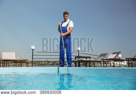 Worker Cleaning Outdoor Swimming Pool With Underwater Vacuum