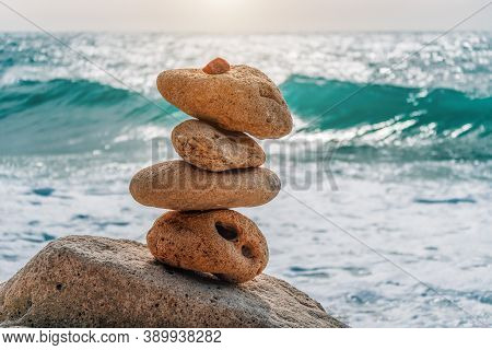 Balanced Pebble Pyramid On The Beach On A Sunny Day. Sea Foam On The Background. Selective Focus. Ze