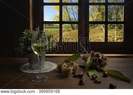 Chestnuts And A Glass Of White Wine On The Table In Front Of The Window On An Autumn Day