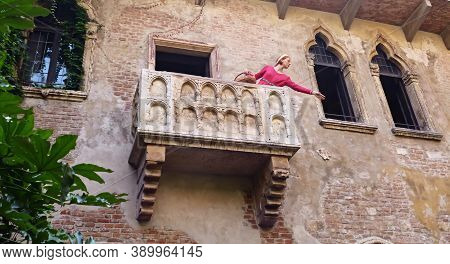 Verona / Italy - September 8, 2012: Woman Wearing Juliet Costume Smiles At Tourists From Juliet And
