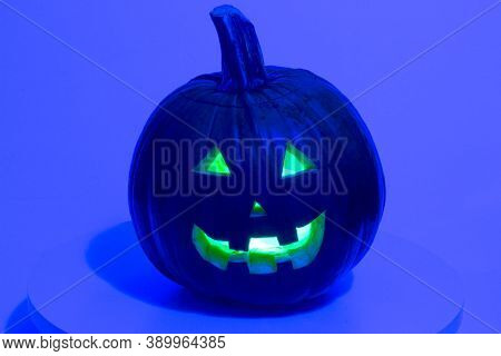 A Black Halloween Pumpkin Jack-o-lantern On A Purple Background.