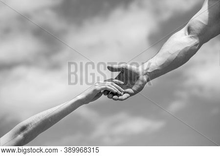 Hands Of Man And Woman On Blue Sky Background. Lending A Helping Hand. Solidarity, Compassion, And C
