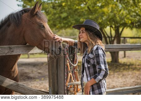 American Woman On A Horse Farm. Portrait Of Girl In Cowboy Hat With A Horses. Hippotherapy At Nature