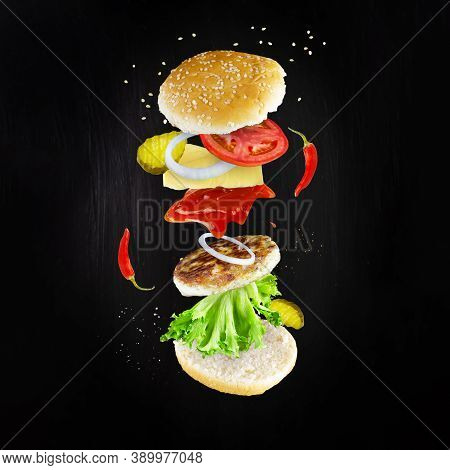 Levitating Spicy Cheeseburger Ingredients On Dark Background. Burger Components Floating In The Air: