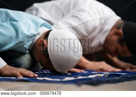Muslim Father And Son Praying Or Performing Salah While Sitting On Prayer Rug And Touching Head To M