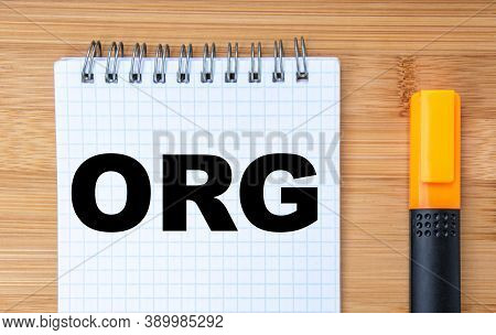 Business Concept. On The Wooden Table Is A Marker And A Notebook With The Inscription Org. Business