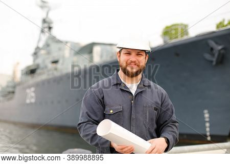 Marine Chies Officer Holding Blueprints And Standing Near Vessel.