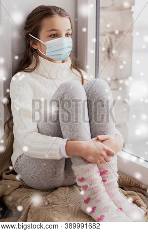 health safety, quarantine and pandemic concept - sad beautiful girl in protective medical mask for protection from virus disease sitting on sill at home window in winter over snow