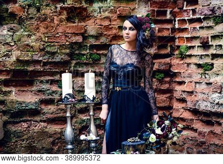 A Girl In A Mystical Dark Image In A Black Dress With Flowers In Her Hair Against The Background Of
