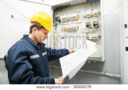 Electrician builder at work inspecting cabling connection of high voltage power electric line in industrial distribution fuseboard poster