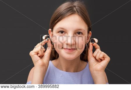 Teenage Girl Showing Her Modern Hearing Aids, Close-up On A Black Background. Selection Of Hearing A