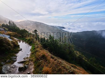 Morning Reflection In I Puddle On A Mountain Ridge Walking Path In A Slope Above The Clouds, Low Tat