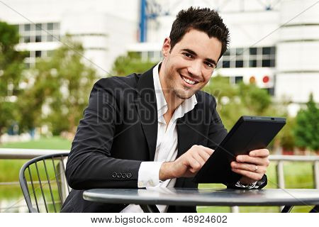 Jonge succesvolle zakenman met tablet buitenshuis
