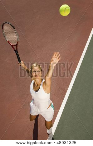 Elevated view of a female tennis player serving ball on court
