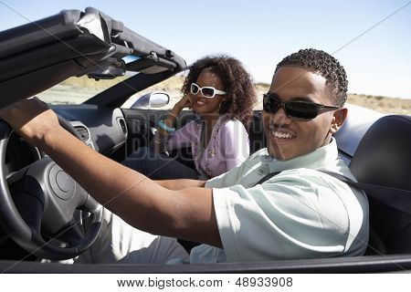 Closeup of a happy African American couple driving convertible on desert road