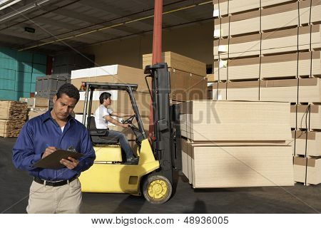 Male supervisor with clipboard in front of forklift stacking boxes at warehouse