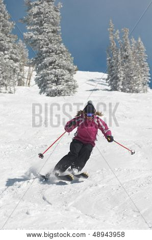 Full length of a young woman skiing down snow covered slope
