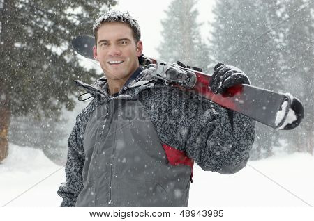 Portrait of a confident young man holding skis on shoulder in snow