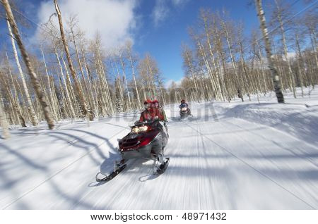 Two couples riding on two snowmobiles along the snowy track
