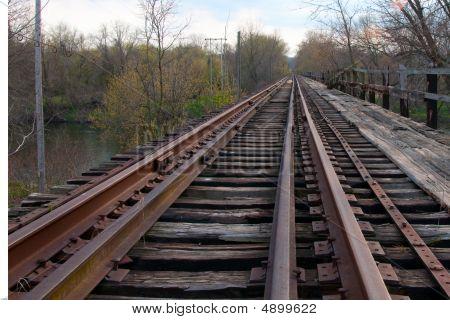 Rusting Railroad Tracks Going Over Bridge
