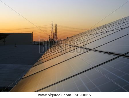 View of solar panels with electrical power lines in the background poster