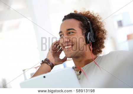 Smiling man listening to music with tablet