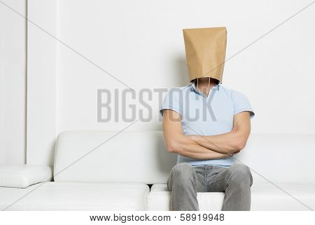 Powerful self confident man with head covered by a blank paper bag sitting on sofa with arms crossed,  empty space for text, on white background.