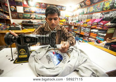 KATHMANDU, NEPAL - DEC 20: Unidentified Nepali man does embroidery on clothes in a small workshop, Dec 20, 2013 in KTM, Nepal. Nepal is one of poorest countries of world, unemployment rate of 46 %.