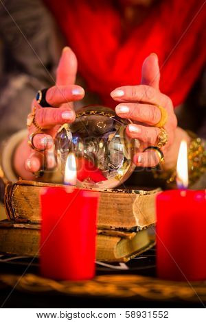 Female Fortuneteller or esoteric Oracle, sees in the future by looking into their crystal ball during a Seance to interpret them and to answer questions