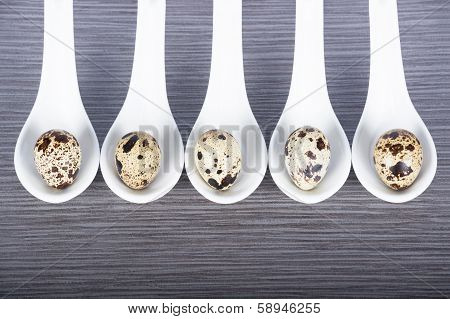 Group Porcelain Spoons And Quail Eggs On A Gray Background