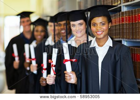 group of happy graduates holding diploma in library