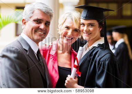beautiful female college graduate with parents on graduation day