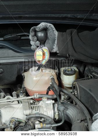 Auto mechanic performing antifreeze coolant freeze-up protection test using a tester