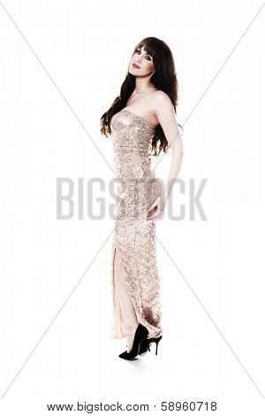 Beautiful young woman with long brunette hair posing standing sideways in an elegant metallic silver evening gown looking at the camera with a lovely smile, isolated on white