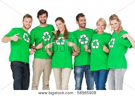 Group portrait of young people in recycling symbol t-shirts pointing to themselves over white background