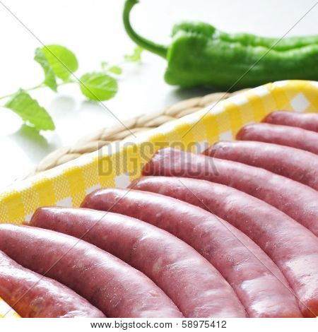 a pile of uncooked sausages in a plastic tray on a kitchen worktop